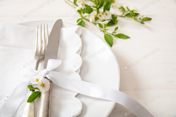 Holiday table place setting with plates, fork and knife