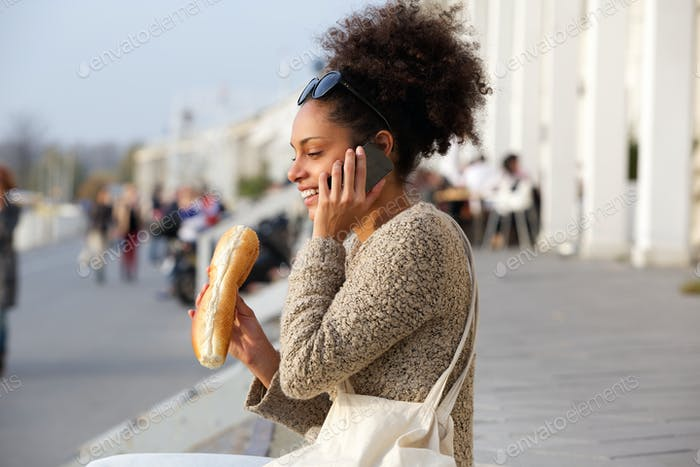 Happy woman eating and talking on mobile phone