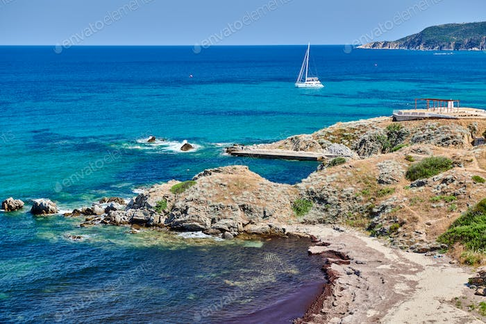 Rocky coastline landscape with yacht