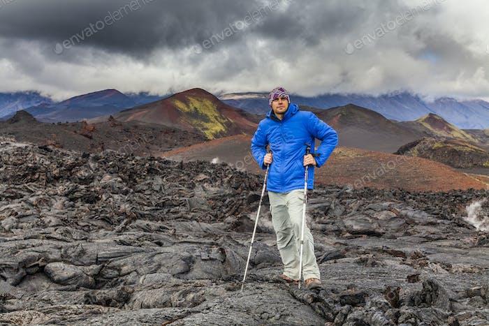 Junge Reisende auf einem Hintergrund von Vulkangestein. Kamtschatka.