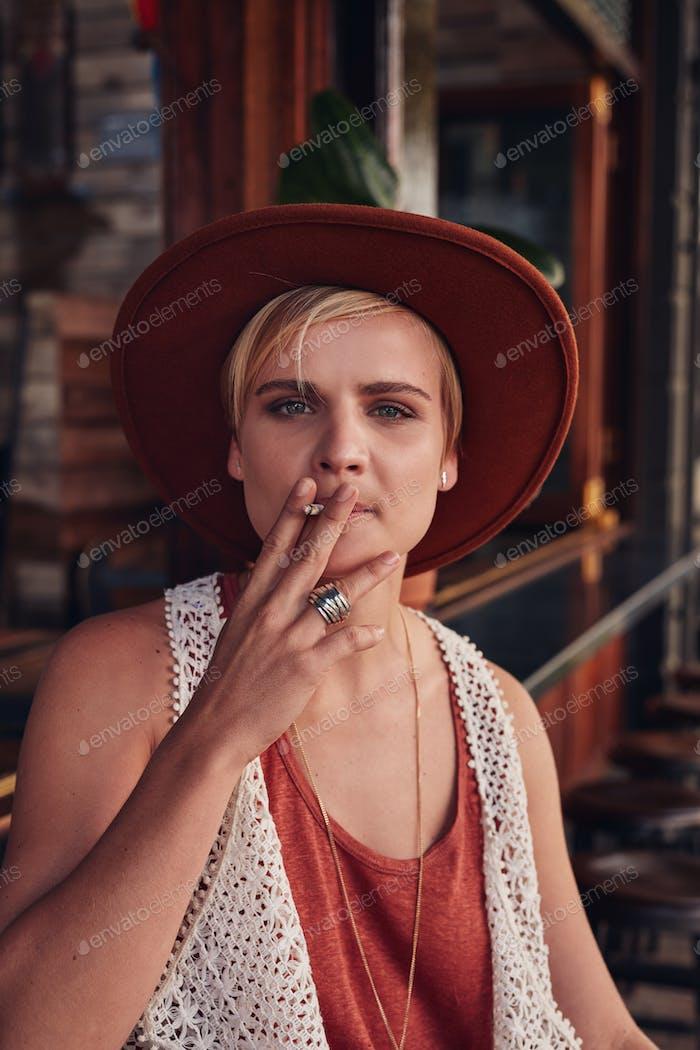 Junge Frau eine Zigarette im Café rauchen