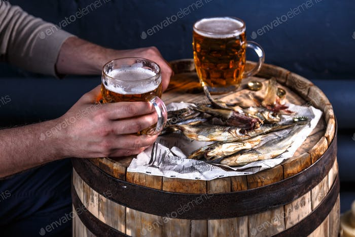 Man drink beer with dried fishes