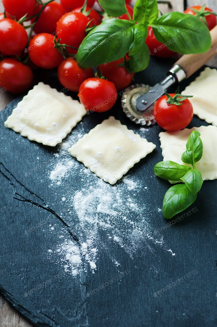 Uncooked ravioli with tomato and basil