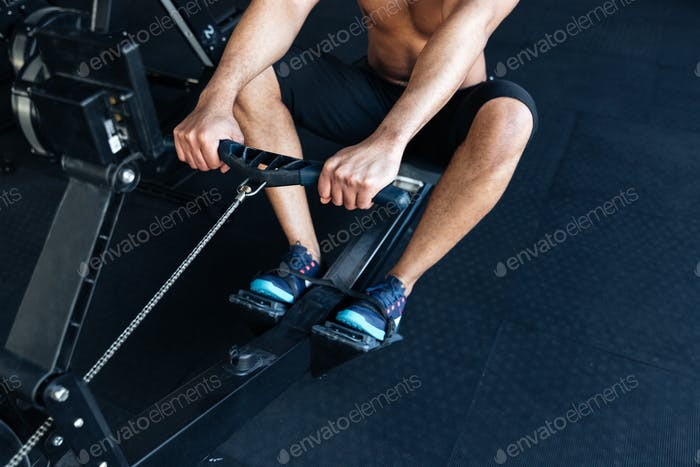 Muscular fitness man using rowing machine in the gym