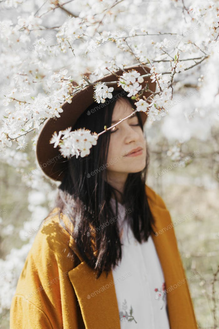 Blooming cherry branches in sunny spring on background of blurred stylish woman in hat, calm moment