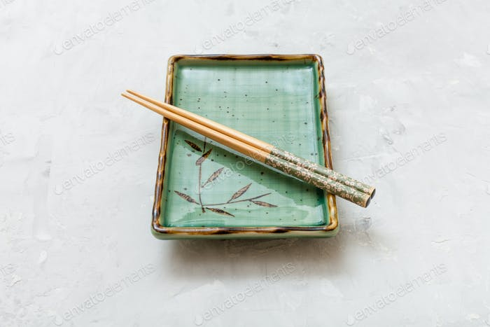 green plate with chopsticks on concrete surface