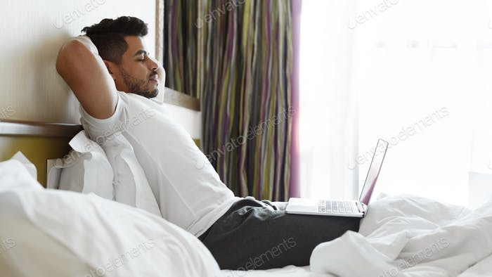 Relaxed handsome man listening to music in bed, using laptop
