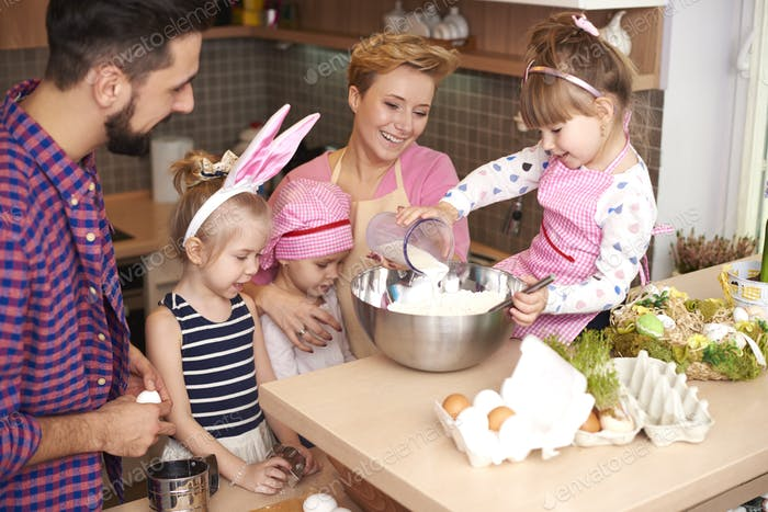 Mother teaching daughters how to bake