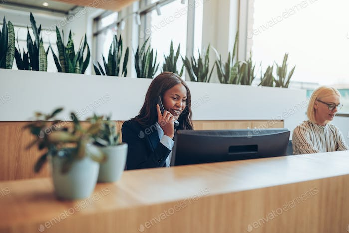 African American businesswomen talking on an office telephone and smiling