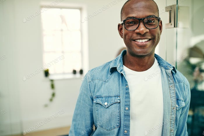 Smiling African businessman standing in a modern office