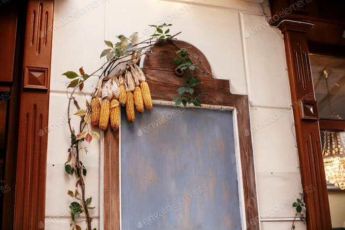 Corn on wooden board with space for text in city street, holiday autumnal decoration of store fronts