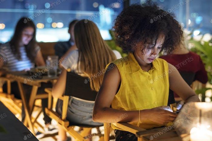 Junger Erwachsener auf einem Abendessen Date mit einem Smartphone-Sucht Concep