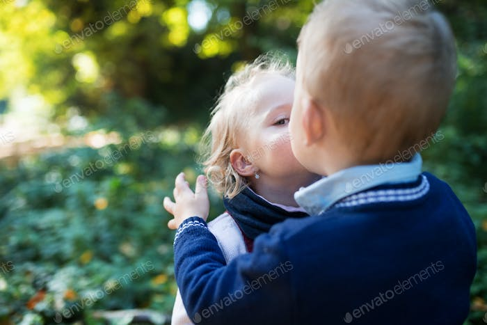 Twin toddler sibling boy and girl standing in autumn forest, kissing