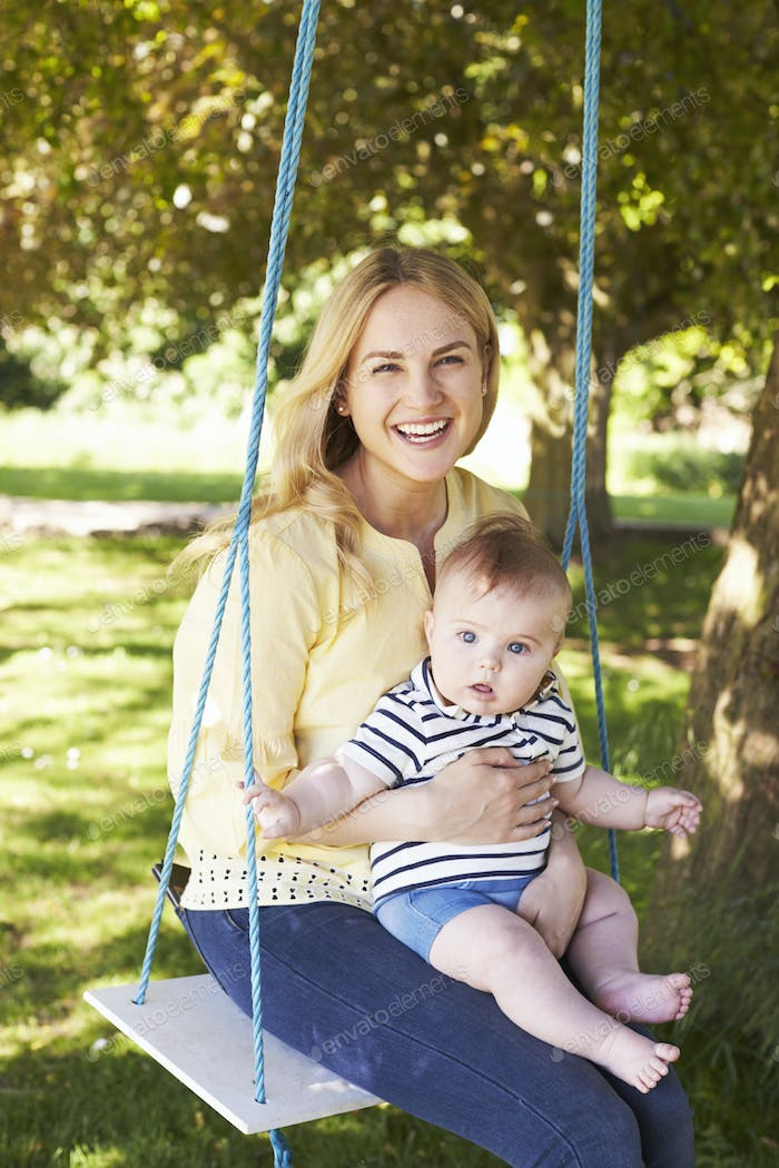 Portrait Of Mother Playing With Baby Son On Garden Swing