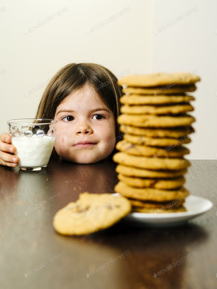 Young girl staring at pile of cookies