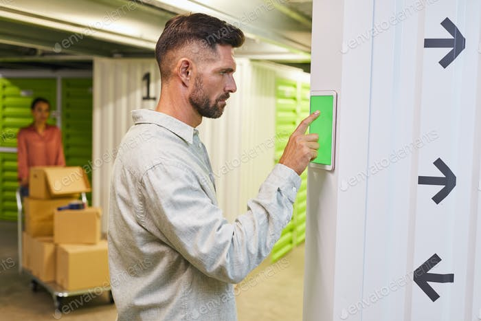 Man Using Control Panel in Self Storage Unit
