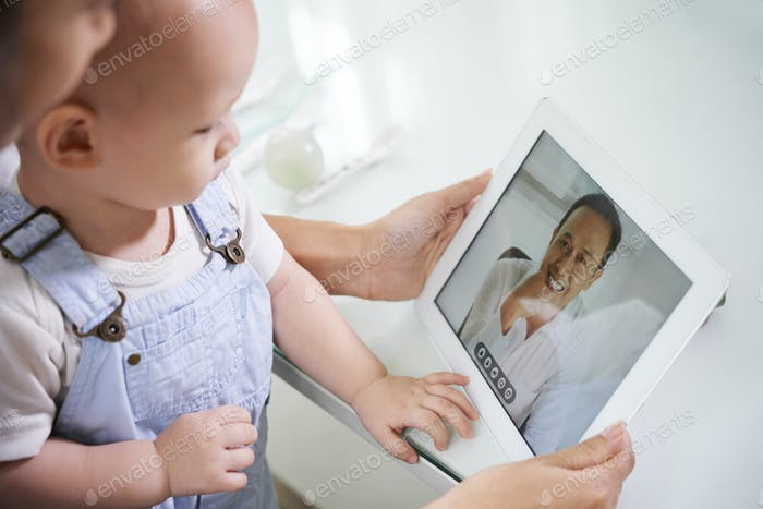 Woman with baby video calling husband