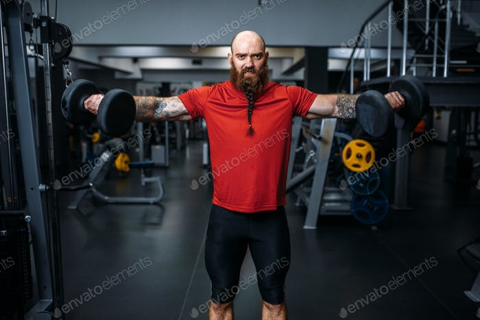 Weightlifter doing exercise with dumbbells in gym