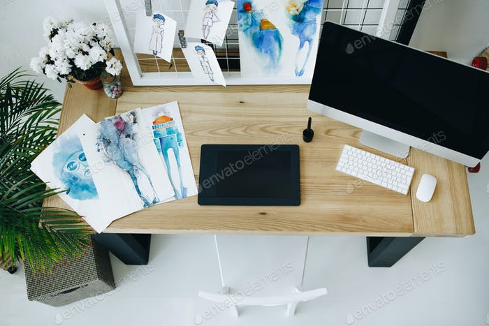 high angle view of graphic tablet, desktop computer and sketches in fashion design studio
