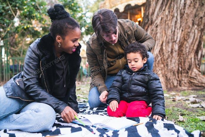 Смешанная расовая этническая семья в парке.