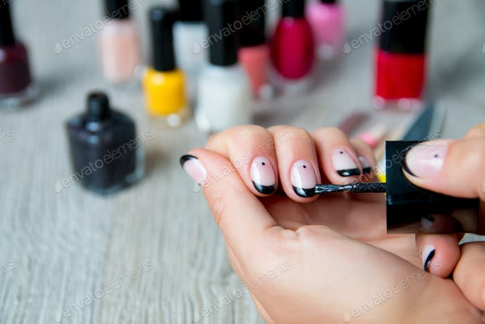 Thumbnail for Black nail polish being applied to hand with tools for manicure on background.