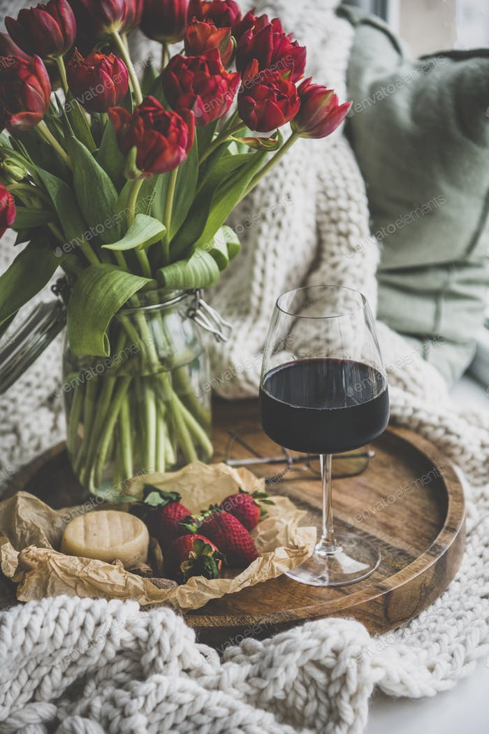 Glas Rotwein, Snacks und Frühlingsrote Tulpen