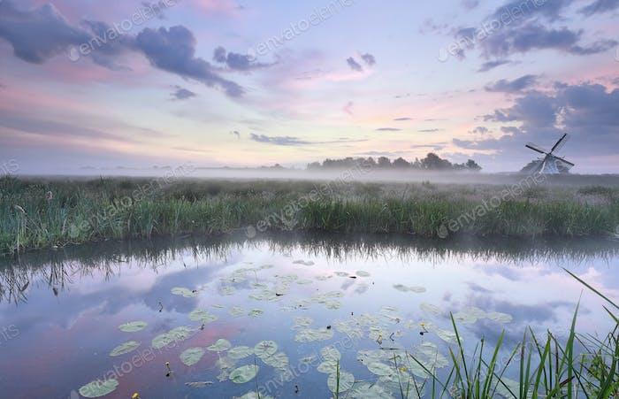 Molino de viento holandés en el lago en el Amanecer brumoso