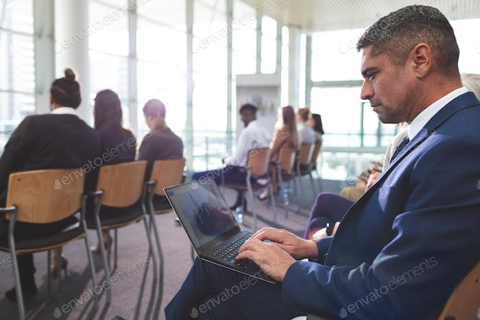 Side view of mixed race businessman using laptop during business seminar in office building