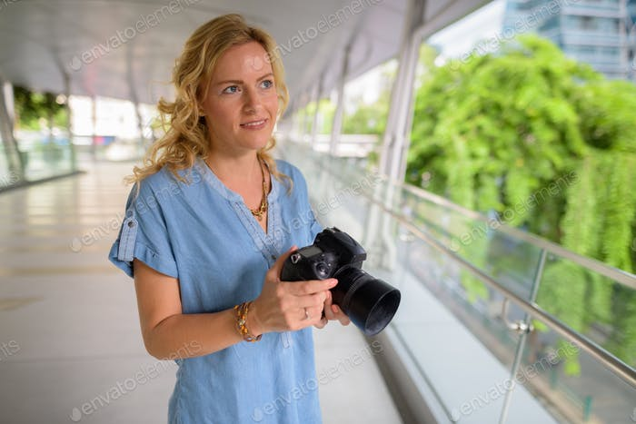 Beautiful blonde tourist woman photographer using camera outdoors