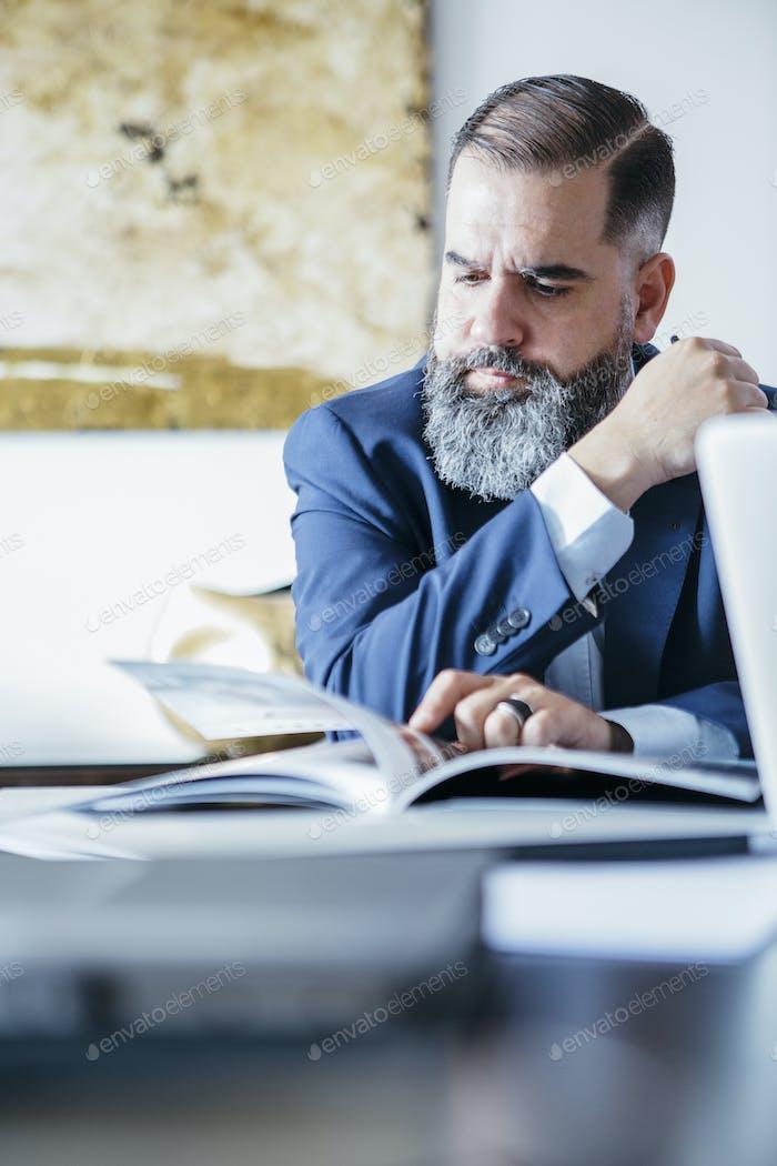 Portrait of bearded man reading magazine