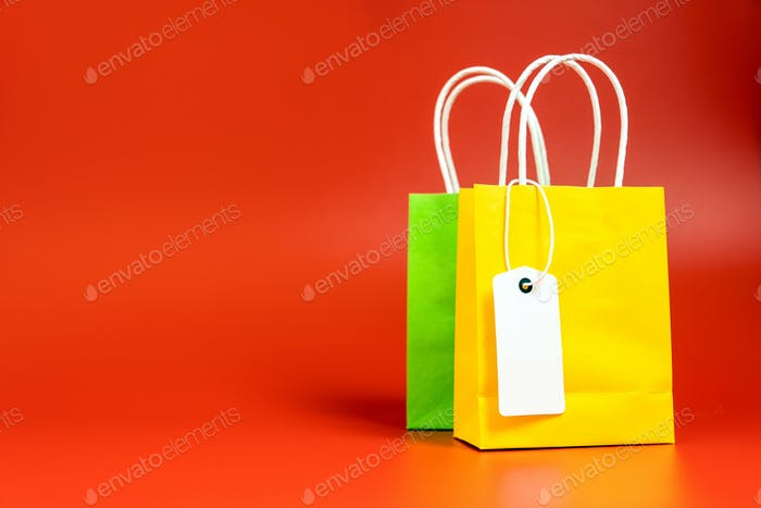 Yellow and green shopping or gift bags isolated on red