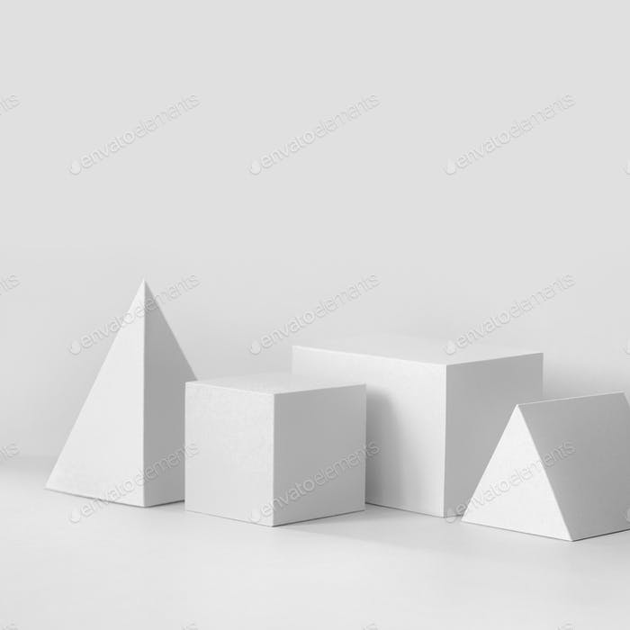 White geometrical figures still life composition. Prism pyramid rectangular cube objects, copy space