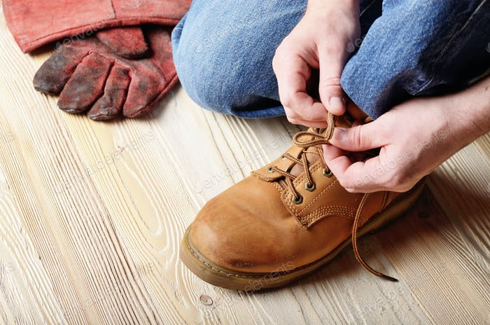 Carpenter in blue jeans tying shoelaces of yellow work boots on