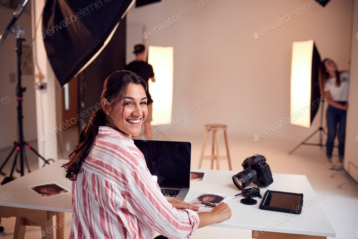 Portrait Of Professional Female Photographer Working In Studio With Assistants