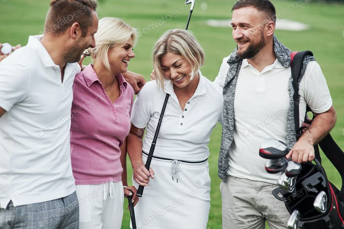 Hugs and close up look. Cheerful friends spending time in the golf field with sticks and good mood