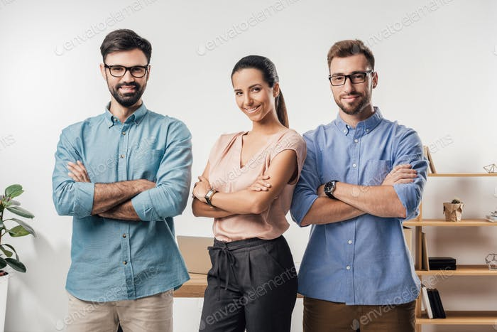 portrait of smiling business people with crossed arms standing at workplace in office