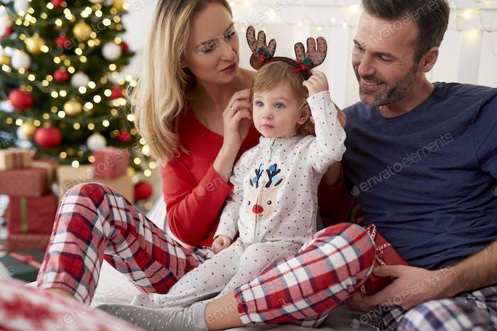 Glückliches Baby mit Familie am Weihnachtsmorgen