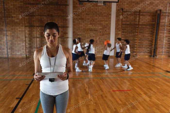 Front view of female basketball coach using digital tablet at basketball court in school