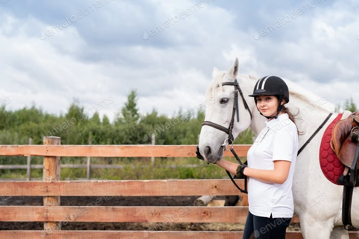 Young woman in equestrian outfit and white racehorse moving along wooden fence