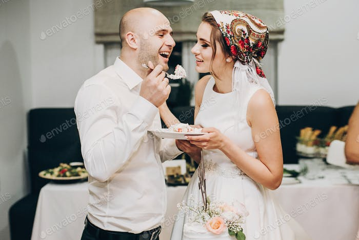 Bride and groom tasting stylish wedding cake at wedding reception
