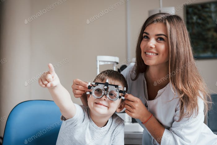 Child sitting in the doctor's cabinet and have tested his visual acuity