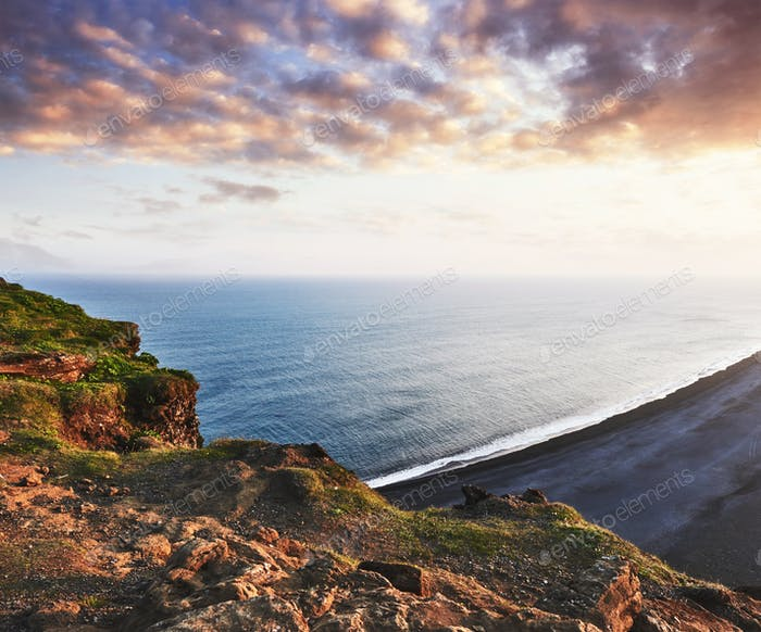 The black sand beach and mountains Reynisfjara from Cape at sunset in Iceland