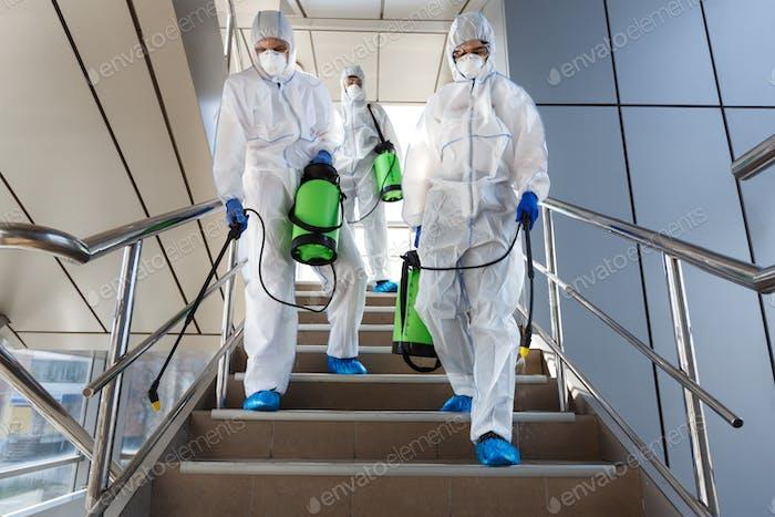 Menschen tragen Schutzanzüge desinfizieren Treppen mit Spray