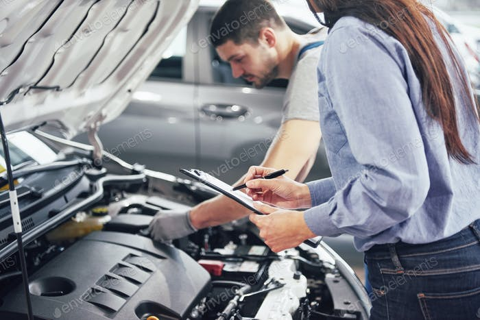 A man mechanic and woman customer look at the car hood and discuss repairs