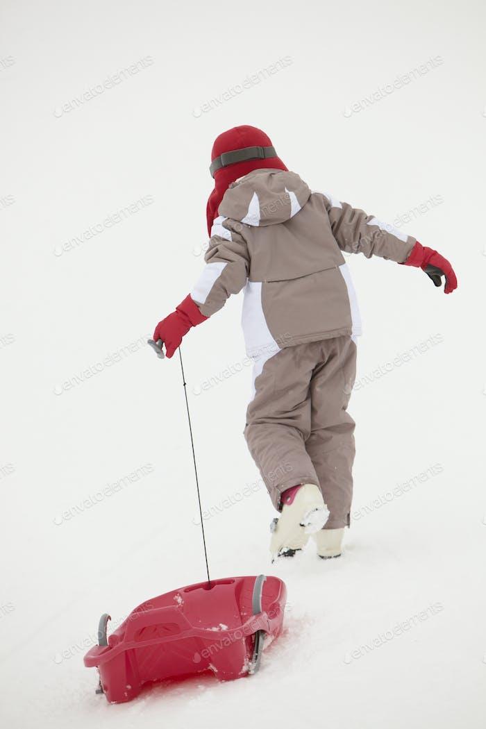Rückansicht Junges Mädchen Ziehen Schlitten Auf Skiurlaub In Bergen