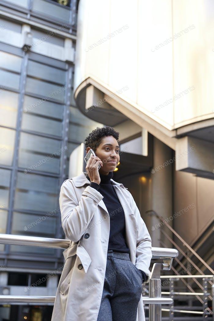 Модные молодые черные бизнесвумен стоя палинг на смартфоне