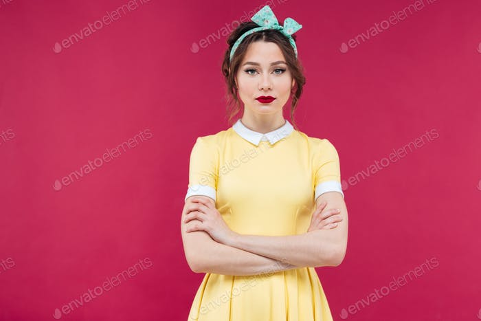 Beautiful serious woman in yellow dress standing with arms crossed