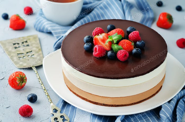 Triple chocolate mousse cake decorated with fresh berries