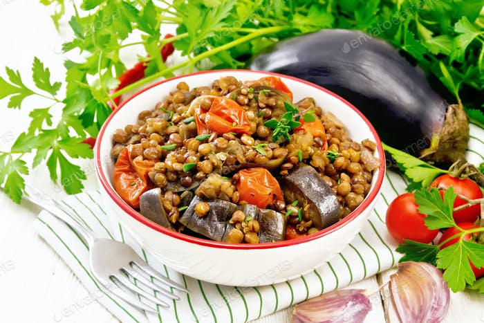 Lentils with eggplant in bowl on napkin