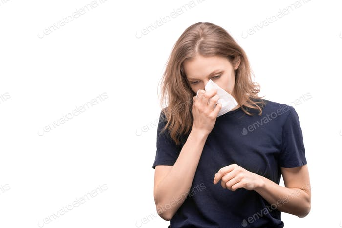 Sick young woman with rhinitis holding handkerchief by blowing nose
